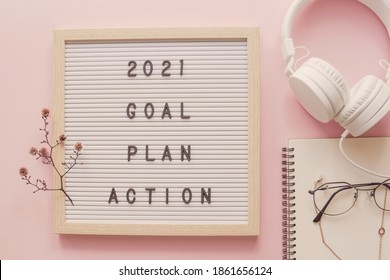 2021 New year resolution, Goal, Plan and action on letter board with notepad and headphone