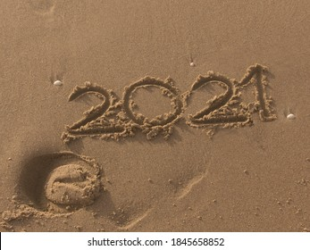 2021 numbers written on the sand of the beach with horses imprint. Textured background with copy space