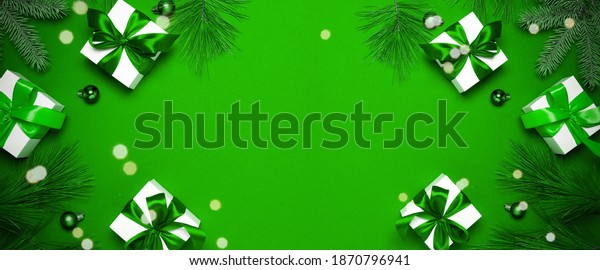2021 White gift box with emerald ribbon, New Year balls and sparkling lights in Christmas composition on dark green background for greeting card. Decoration and copy space for your text.