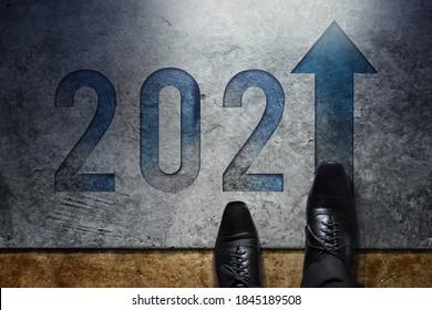 Konzept 2021: Top-Ansicht der Geschäftsleute über formelle Business Shoes, die auf dem Fußboden stehen, um in Number and Forward Arrow zu gehen
