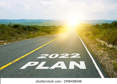 2022 Plan, concept photo of asphalt road. Motivational inscription on the road going forward. The beginning of a new path. A conceptual photo of the path leading to a bright future.
