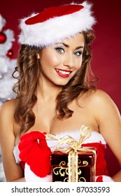 20-25 years olf beautiful woman next to christmas tree on red background