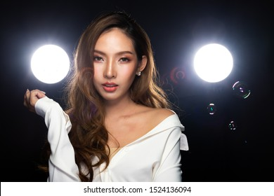 20s Asian Beautiful woman Blonde Brown dying color Curly style Hair wear White shirt smile look to camera in portrait half body.  Studio Dark background two backlit with puffy smoke, Fog, bubble