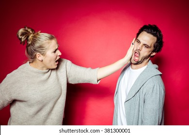 20s Couple in Photostudio in front of beige backdrop having fun fighting in front of the camera with spot light with contrasty vibrant look kissing each other
