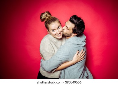 20s Couple in Photostudio in front of beige backdrop having fun in front of the camera with spot light with contrasty vibrant look kissing each other