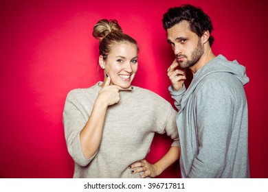 20s Couple in Photostudio in front of beige backdrop having fun in front of the camera with spot light with contrasty vibrant look
