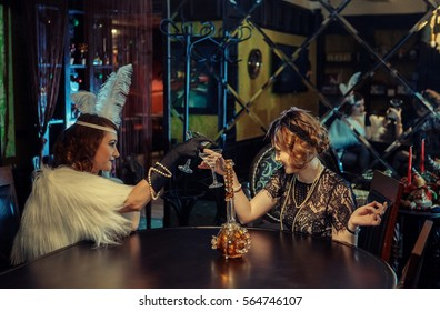 20s style concept. Two pretty ladies in vintage dresses dancing and drinking in old-fashioned interior. Having fun