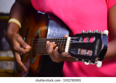 20th April 2020, Ibadan, Oyo State, Nigeria. A young lady playing an acoustic guitar