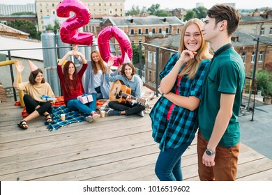 20th birthday surprise. Girl is happy and smiling. Friends sit on a rooftop with balloons. Celebration, congratulation, youth friendship and support
