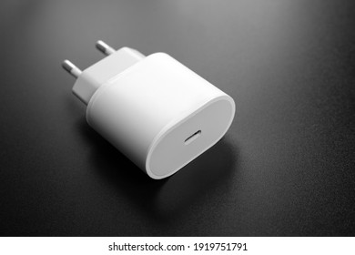 20W USB-C Power Adapter. power supply for charging the phone on a black background