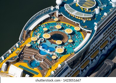 21 April 2019, IJmuiden, Holland. Aerial view of deck at cruise ship AIDA LUNA at passengers terminal in IJmuiden. People lay in blue swimming pool or relax in the sun.
