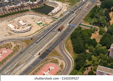 21 July 2018, Amsterdam, Holland. Aerial view of a construction site, a train at station North at the Noord Zuid Lijn and a highway.. The subway line connects the North of Amsterdam with the South.