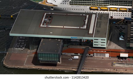 21 June 2018, Amsterdam, Holland. Aerial bird view of concert hall Muziekgebouw in the Amsterdam harbor. In the back part of a large cruise ship.