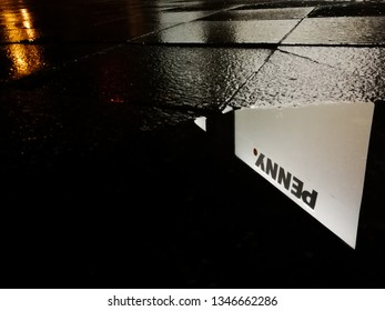 21 March 2019, Berlin, Germany. Penny Market logi sign reflected in a puddle at night.