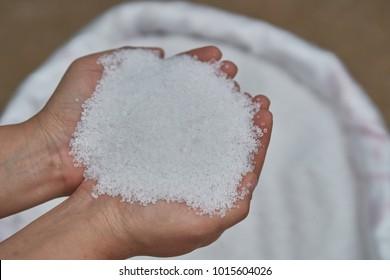 21-0-0,Ammonium sulfate,  Mohrs Salt. Fertilizer in farmer hands over white fertilizer bag.