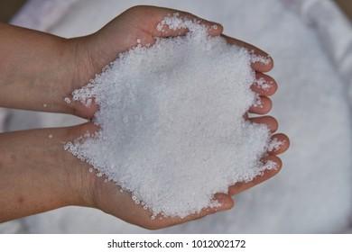 21-0-0,Ammonium sulfate, (NH4) 2SO4,  Mohrs Salt. Fertilizer in farmer hands over white fertilizer bag.