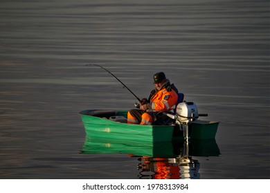 21-05-02021 Riga, Latvia Fishing boat and fisherman in sea at dawn.