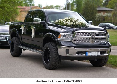 21.05.2021, Riga, Latvia, A black wedding car decorated with white roses, just married.