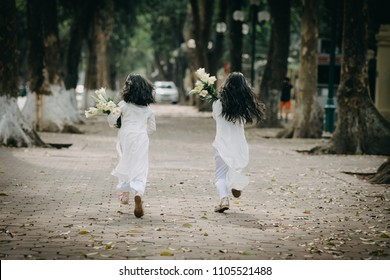 211/5000 Two little girls dressed in traditional Vietnamese costume on the road with beautiful trees at sunset in Hanoi, Vietnam.