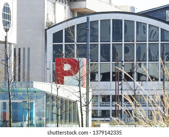 21st of April 2019 -Cityscape with view past Musikkens Hus (House of Music) and a red P at the entrance to a basement car parking to the former powerplant Nordkraft, Aalborg, Denmark