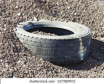 21st of April 2019 - Scene from Danish harbor with close up of a tire in a pile of Leca lightweight aggregate, Aalborg, Denmark