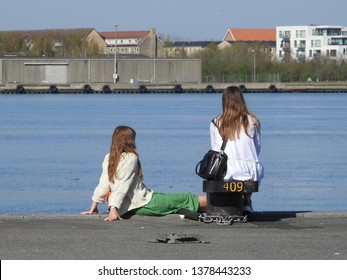 21st of April 2019 - Scene from a Danish port with two girls sitting on the quay, Aalborg, Denmark