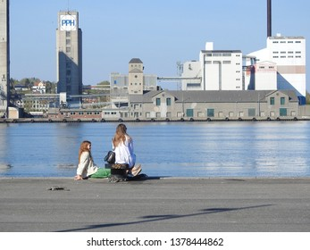 21st of April 2019 - Scene from a Danish port with view past two girls sitting at the quay to industrial buildings on the other side of the water, Aalborg, Denmark