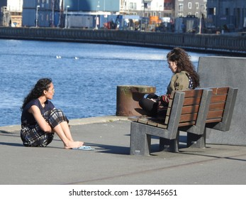 21st of April 2019 - Scene from a Danish port with  two girls sitting at the quay, Aalborg, Denmark
