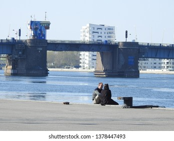 21st of April 2019 - Scene from a Danish port with view past a young couple at the quay to a bridge and a skyline on the other side of the water, Aalborg, Denmark