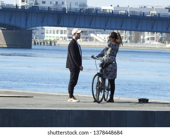 21st of April 2019 - Scene from a Danish port with view past standing couple to the fiord and a bridge, Aalborg, Denmark