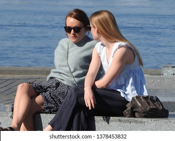 21st of April 2019 - Scene from a Danish port with two young women sitting on the quay, Aalborg, Denmark