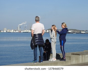 21st of April 2019 - Scene from a Danish port with family standing on the quay enjoying the view, Aalborg, Denamrk