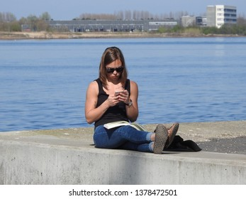 21st of April 2019 - Scene from a Danish port with young woman sitting on the quay checking her smartphone, Aalborg, Denmark