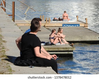 21st of April 2019 - Scene from a danish port with people relaxing on the quay, Aalborg, Denmark