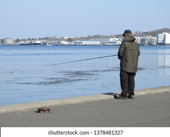 21st of april 2019 - Scene from a Danish port with man standing on the quay fishing, Aalborg, Denmark