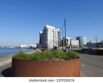 21st of April 2019 - Scene from a Danish port with view past a rusty flower bowl to residential and industrialbuildings against a blue sky, Aalborg, Denmark