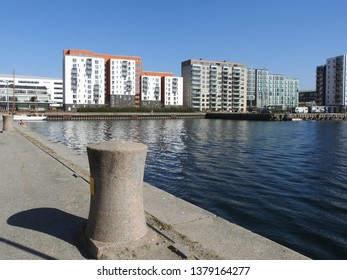 21st of April 2019 - Scene from a Danish port with view past a granite bollard and a dock to new residential buildings against a blue sky, Aalborg, Denmark