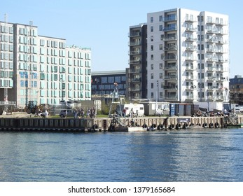 21st of April 2019 - Scene from a Danish port with view past a dock to new residential buildings against a blue sky, Aalborg, Denmark