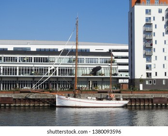 21st of April 2019 - Scene from Danish port with view to a white vessel in front of modern buildings, Aalborg, Denmark