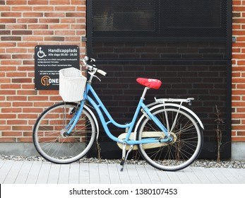 21st of April 2019 -Scene from a Danish city with close up of a blue bicycle with a white basket and a red saddle, Aalborg, Denmark