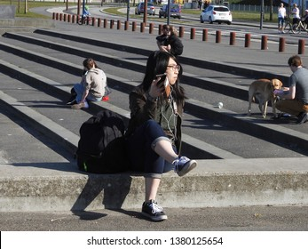 21st of april 2019 - Scene from Dansih city with young Asian woman sitting on a quay with a mobile phone to her ear, Aalborg, Denmark