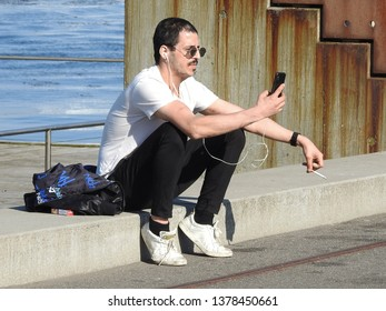 21st of April 2019 - Scene fro Danish port with young man sitting on the quay checking his smartphone, Aalborg, Denmark