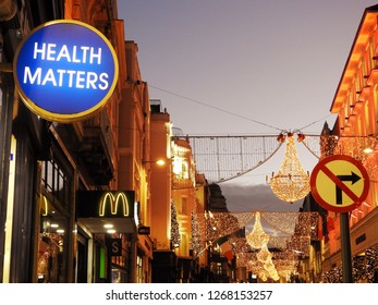 21st December 2018, Dublin. A Health Matters sign on a Christmas lights decorated Grafton Street in the evening light, with a McDonald's logo and No Right Turn symbol sign in the background.