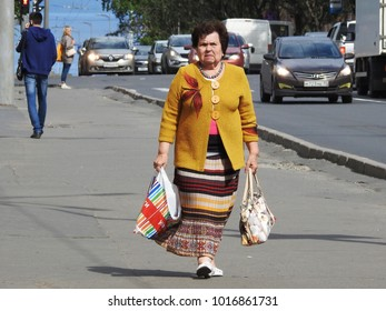 21st of July 2017 - Scene from Russian city with elderly woman strolling along the sidewalk carrying a shopping bag and a handbag, Petrozavodsk, Russia