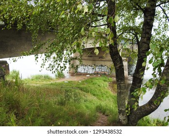 21st of July 2018 - Scene from Russian riverside with view past a birch tree to a bridge pier, Ust-Luga, Russia