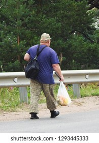 21st of July 2018 - Scene from Russian highway with a red haired man walking along a crash barrier carrying a shoulder bag and a transparent plastcic bag with fish, Ust-Luga, Russia