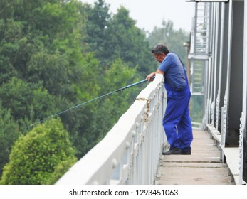 21st of July 2018 - Scene from a Russian river with a local angler standing with his fishing pole by the rail of a bridge, Ust-Luga, Russia