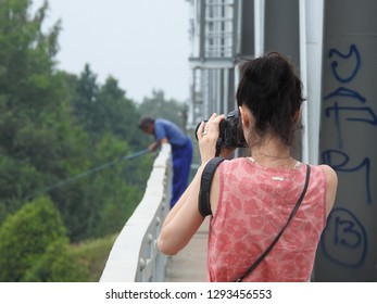 21st of July 2018 - Scene from Russian river with view past a young female photographer on a bridge to a blurred, blue angler, Ust-Luga, Russia