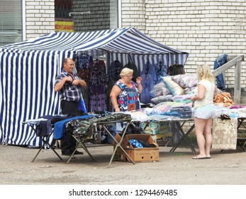 21st of July 2018 - Scene from Russian city with people in front of a blue and white striped tent at a market stall, Ust-Luga, Russia