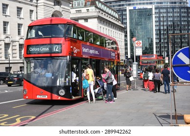 21st June 2015: London, UK, People at St Thomas Hospital Bus Stop in London, station is next to Big Ben, Iconic red color buses at bus stop.